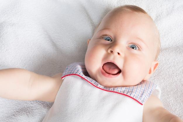 Visage de bébé garçon heureux souriant allongé sur le lit. une photo prise comme un nouveau-né fait un selfie lui-même