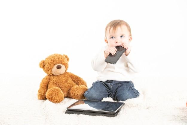 Visage de bébé avec un mobile dans sa bouche à côté d'un ours en peluche et d'une tablette.