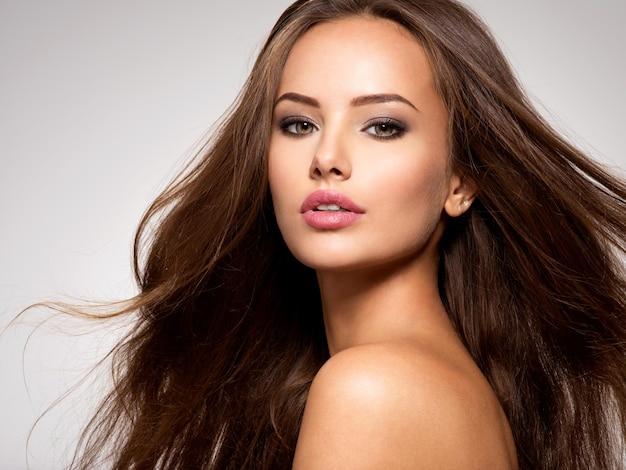 Visage de la belle femme aux longs cheveux bruns posant