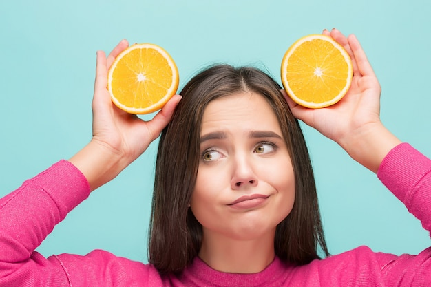 Visage de belle femme avec une délicieuse orange au studio