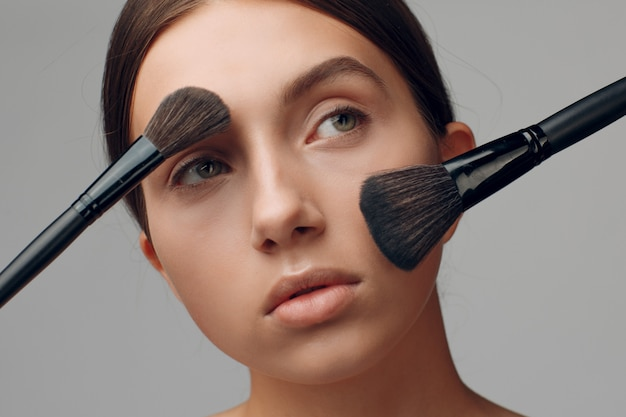 Visage de belle femme avec du maquillage naturel. main de maquilleuse avec pinceau. modèle de beauté jeune femme. maquillage en cours.