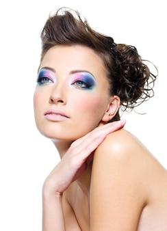 Visage de belle femme avec maquillage lumineux et coiffure créative