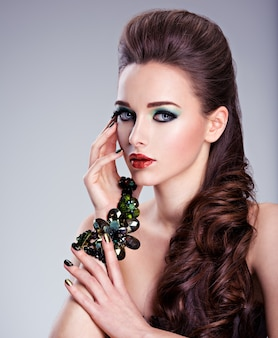 Visage de belle femme avec maquillage mode vert et bijoux en main