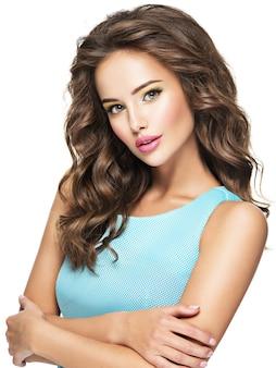 Visage de la belle femme sensuelle aux longs cheveux bouclés. jolie jeune fille avec du maquillage de mode. modèle pose sur fond blanc