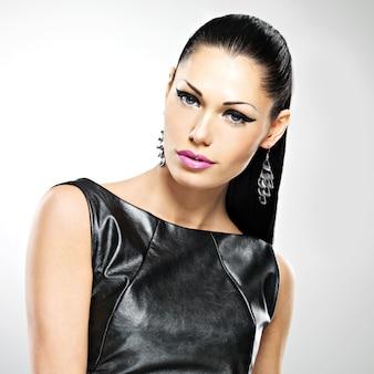 Visage de la belle femme sexy avec maquillage mode glamour des yeux et coiffure brillante. portrait de la jeune fille adulte caucasienne au studio