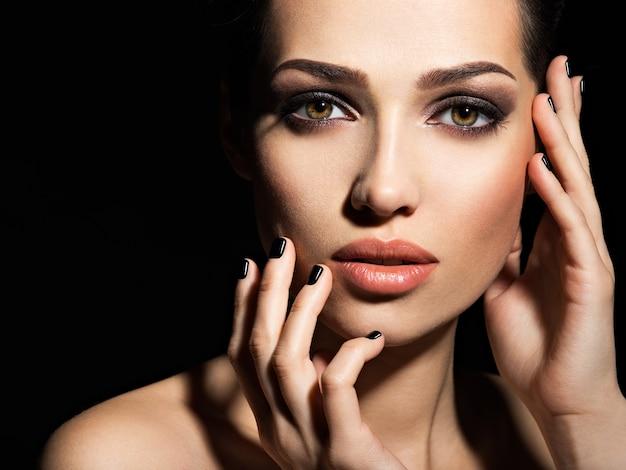 Visage d'une belle fille avec du maquillage de mode et des ongles noirs posant au studio sur fond sombre