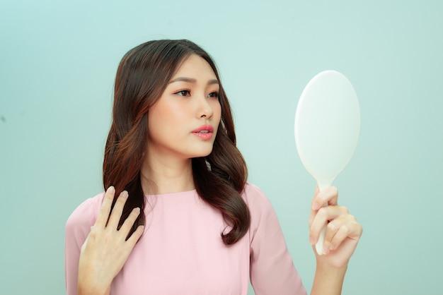 Visage de belle jeune femme en bonne santé regardant dans le miroir