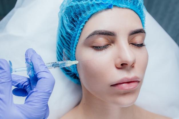 Visage de belle jeune femme et main dans la main avec une seringue faisant l'injection