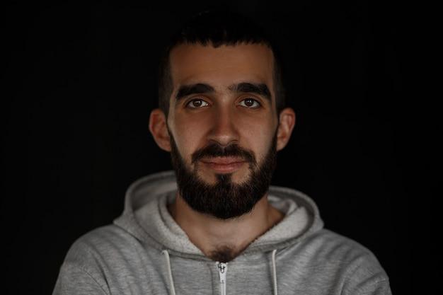 Visage brutal masculin. jeune bel homme avec une barbe dans un sweat à capuche à la mode gris se dresse sur un mur noir