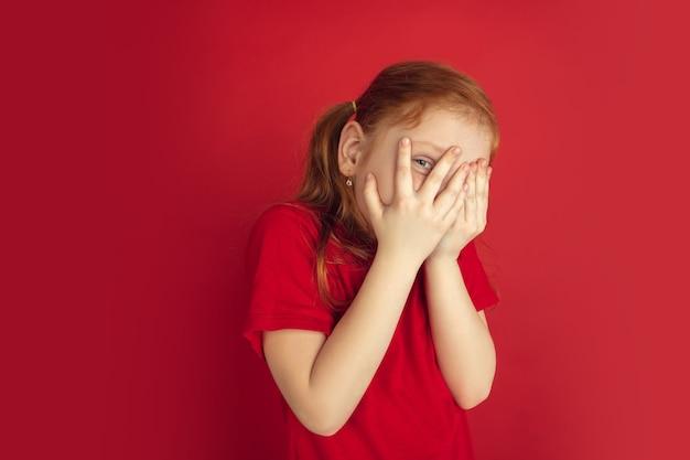 Visage caché effrayé. portrait de petite fille caucasienne isolé sur mur rouge. modèle redhair mignon en chemise rouge. concept d'émotions humaines, expression faciale. espace de copie.