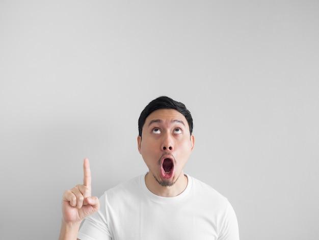 Visage choqué de l'homme asiatique en chemise blanche sur fond gris.