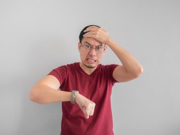 Visage en colère et désagréable de l'homme asiatique regarde sa montre en attendant quelqu'un.