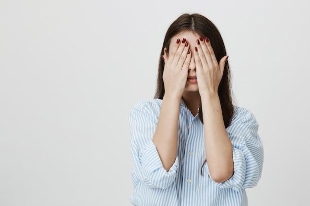 Visage de couverture de femme avec les mains
