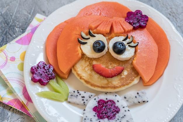 Visage de crêpe drôle de fille avec des fruits