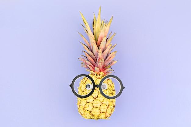 Visage drôle d'ananas jaune avec des lunettes sur violet.