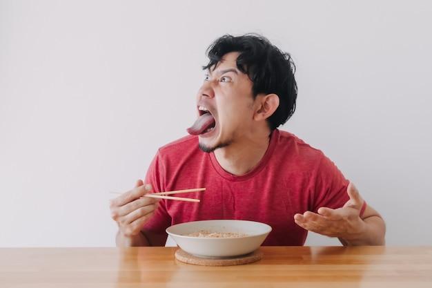 Le visage drôle de l'homme mange des nouilles instantanées très chaudes et épicées