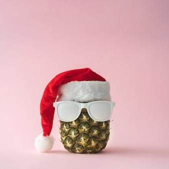 Visage du père noël fait d'ananas et de lunettes de soleil peintes en blanc. concept de noël.