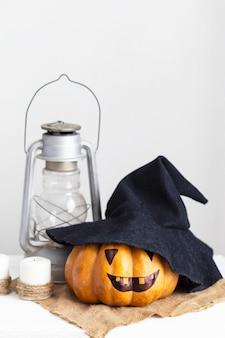 Visage effrayant citrouille, bougies et lanterne sur bois blanc