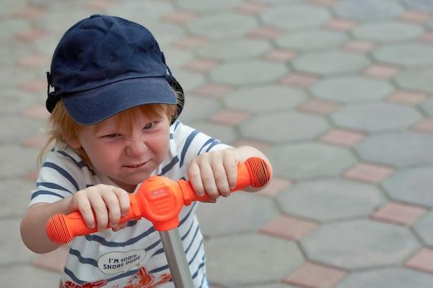 Le visage d'un enfant avec une émotion lumineuse sur le visage d'un scooter