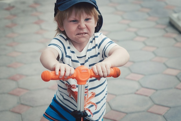 Le visage d'un enfant avec une vive émotion sur le visage d'un scooter. exprimer les émotions de l'enfant