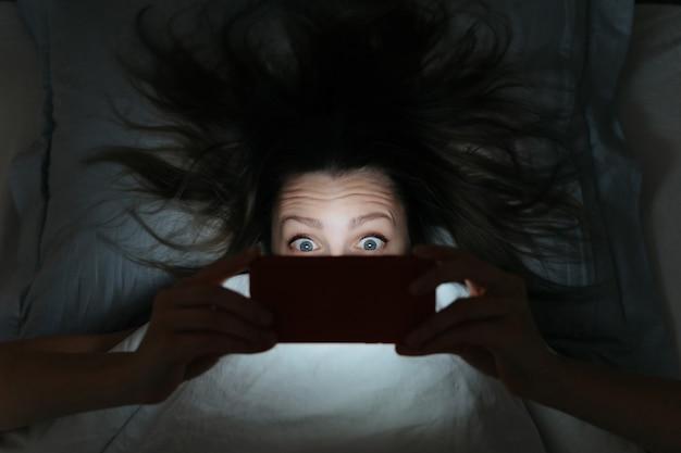 Visage étonné de jeune femme regardant son smartphone tard dans la nuit au lit.