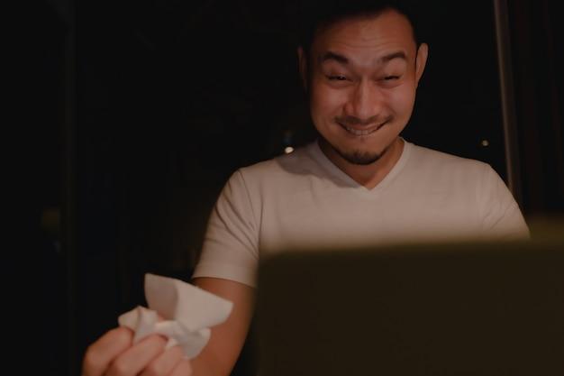 Visage excité drôle d'homme asiatique regardant du porno la nuit.