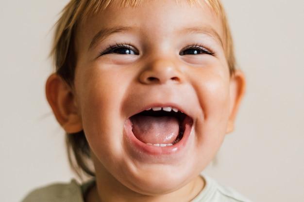 Visage excité d'un petit bébé sur fond blanc