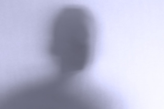 Visage fantôme effrayant défocalisé derrière un verre blanc