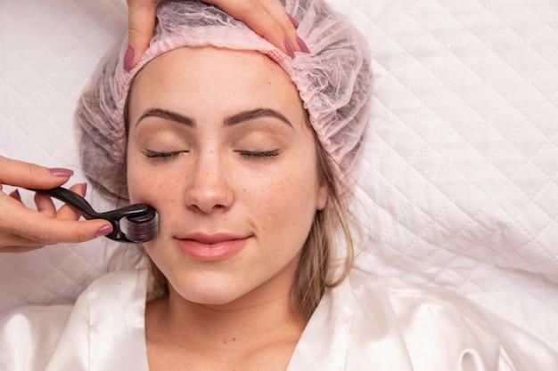 Visage féminin en gros plan avec dermaroller pour les procédures de mésothérapie, soins de la peau à la maison et en salon. rouleau méso avec micro-aiguilles.