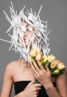 Visage de femme asiatique étant recouvert de plastique blanc tout en tenant des fleurs
