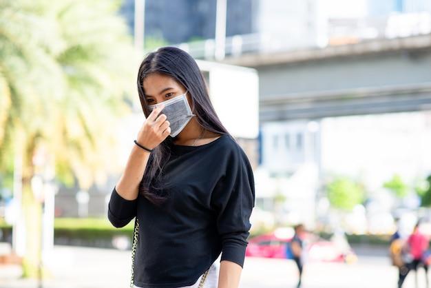 Visage de femme asiatique portant un masque facial pour la protection contre le virus ou la pollution avec fond de ville en plein air.