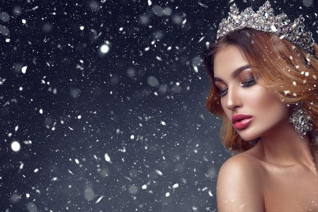 Visage de femme beauté avec de belles couleurs de maquillage. l'image de la reine. des cheveux foncés, une couronne sur la tête, une peau claire, un beau visage, des lèvres charnues.