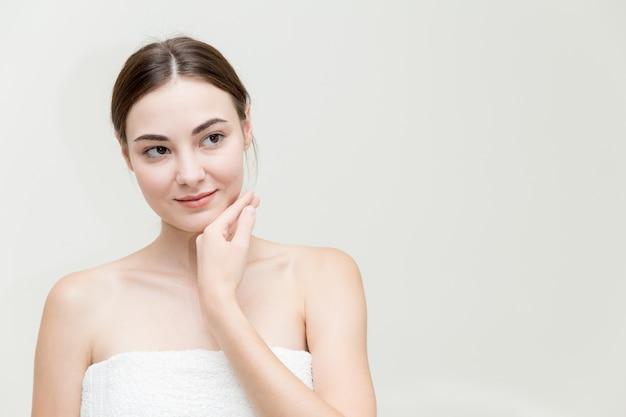 Visage de femme de beauté avec la main présente sa forme de visage isolée sur studio blanc