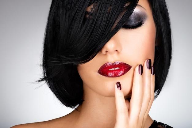 Visage d'une femme avec de beaux ongles foncés et des lèvres rouges sexy. mannequin aux cheveux noirs
