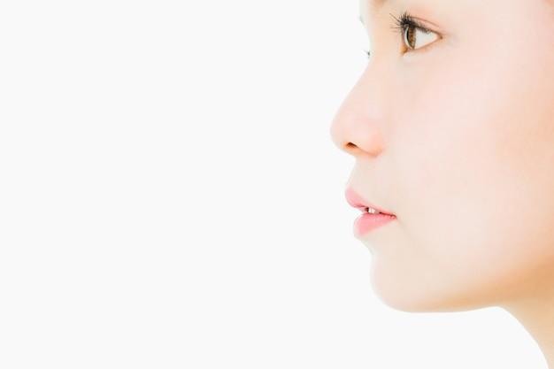Le visage d'une femme avec une bonne santé de la peau et des lèvres roses. les yeux sont impatients.