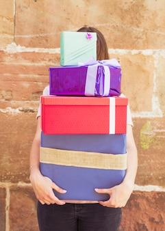 Visage de femme caché par des cadeaux empilés