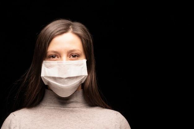 Le visage d'une femme dans un masque, une flambée d'infection à coronavirus et sa protection. fermer