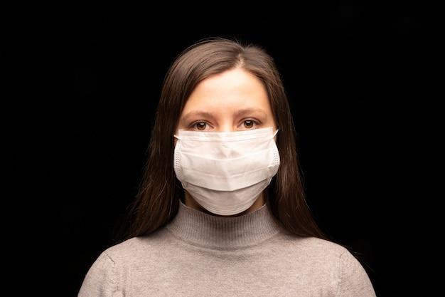 Visage d'une femme dans un masque médical blanc.