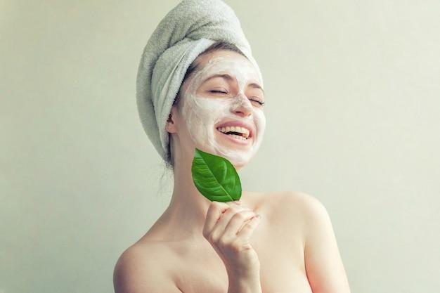 Visage de femme avec feuille verte et crème ou masque nourrissant