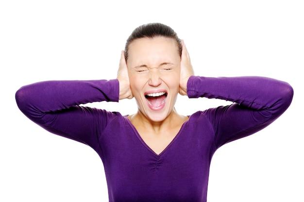 Visage de femme hurlant serrer ses oreilles à la main