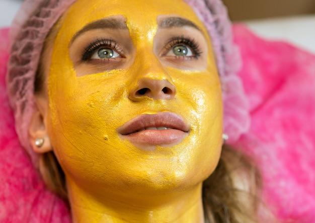 Visage de femme avec masque facial de cosmétologie