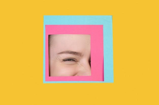 Visage de femme de race blanche furtivement à travers la place en fond jaune