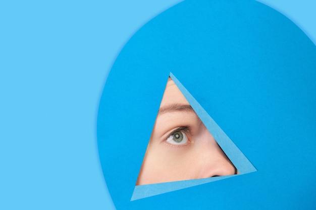 Visage de femme de race blanche peeking throught triangle en fond bleu