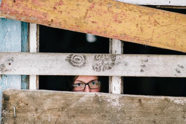 Visage de femme regardant à travers la vieille fenêtre en bois.