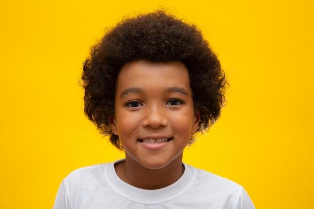 Visage de garçon afro-américain avec des cheveux noirs sur jaune. enfant noir souriant avec un cheveu noir. garçon noir avec des cheveux noirs. descendance africaine.