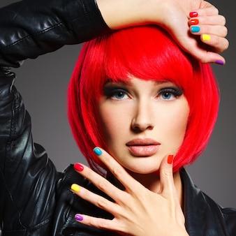 Visage gros plan d'une belle fille avec des ongles multicolores brillants.