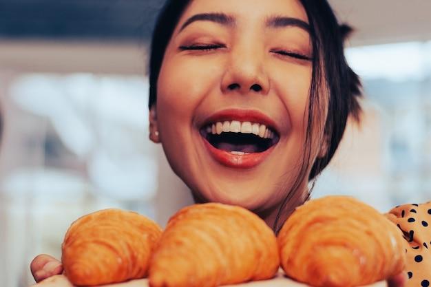 Visage gros plan femme heureuse avec parfum croissant en boutique