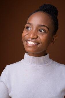 Visage d'heureuse jeune belle femme africaine souriante en pensant