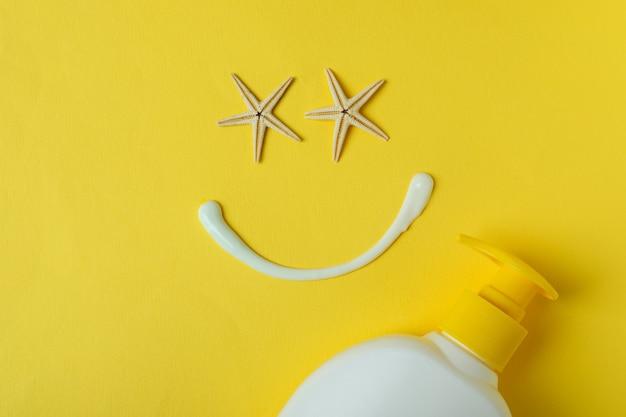 Visage heureux en crème solaire et étoiles de mer sur jaune