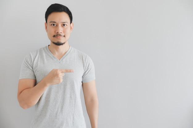 Visage heureux de l'homme en t-shirt gris avec la main point sur l'espace vide.